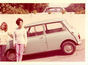 Photo of Bubbles Hair Salons founder Ann Ratner as a teenager standing next to her first car, a light blue Mini