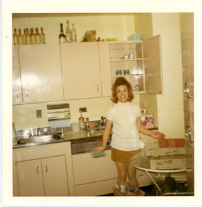 Photo of Bubbles Hair Salons founder Ann Ratner as a young woman in a 1960s era kitchen wearing a mini skirt