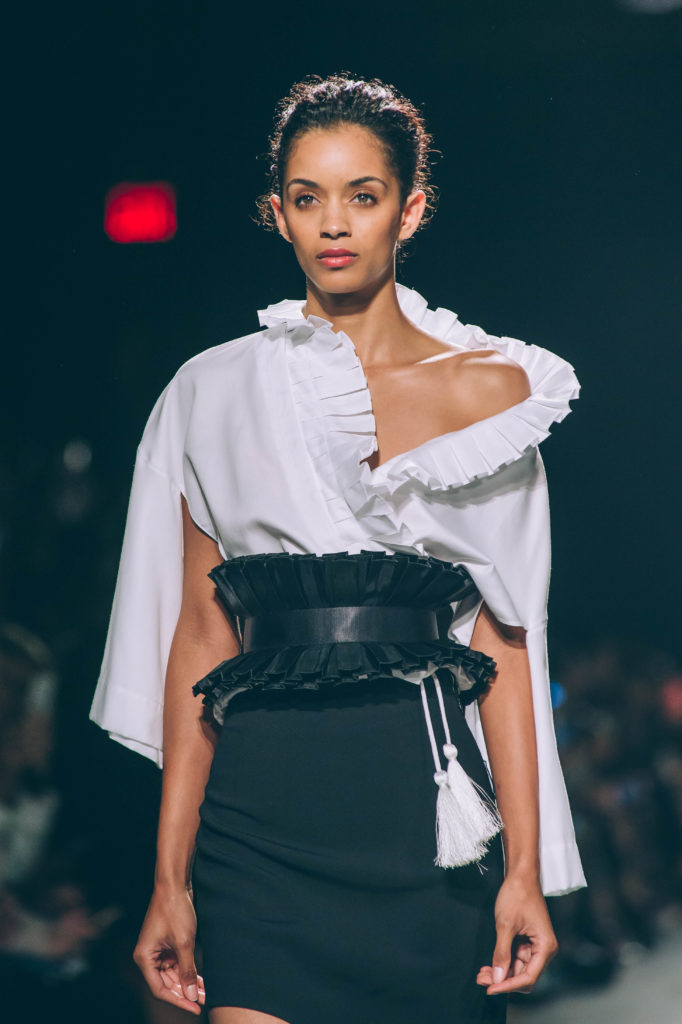 Toaray Wang S/S 2018 sends models down New York Fashion Week runways in black blouse with white ruffles and corset style belt