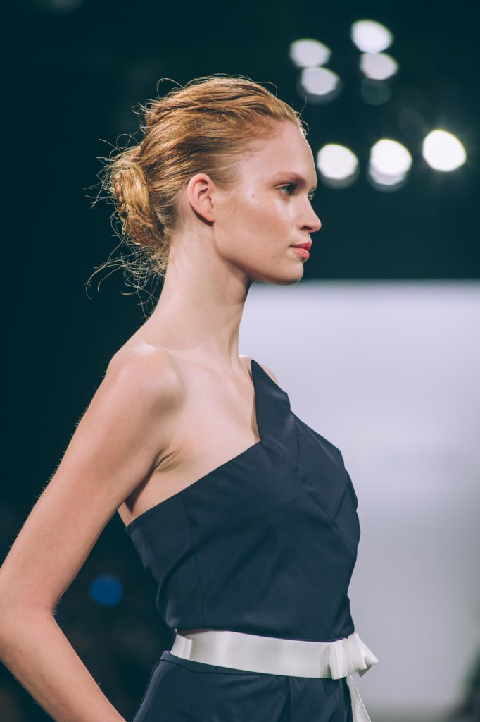 Image of model in black dress with white sash wearing textured updo created by Rodney Cutler for Bubbles Salons at Taoray Wang show during New York Fashion Week